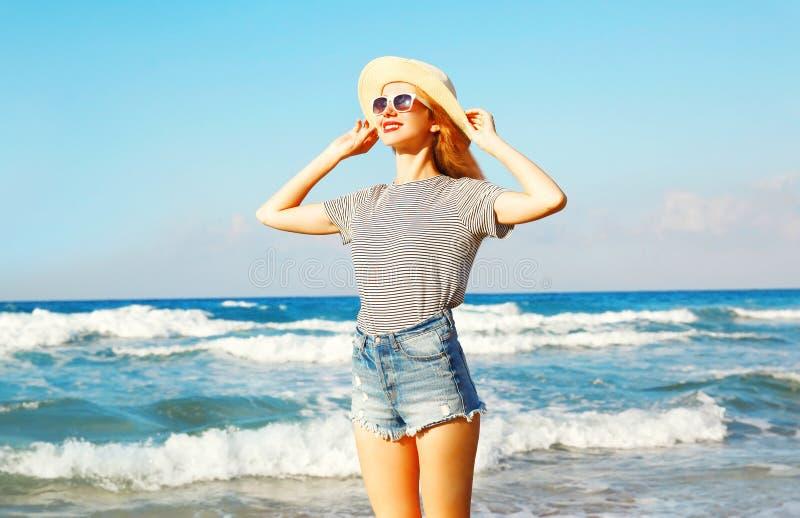 Πορτρέτο της ευτυχούς χαμογελώντας γυναίκας στην παραλία πέρα από τη θάλασσα στο καλοκαίρι στοκ εικόνες