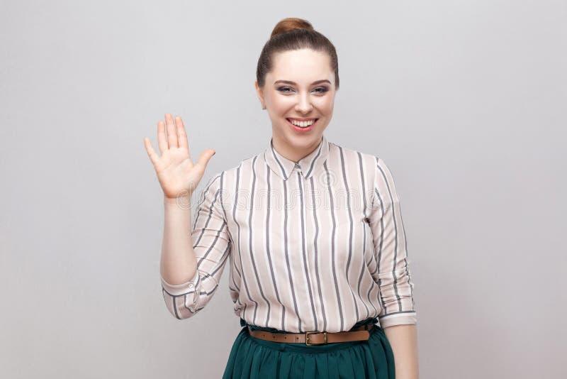 Πορτρέτο της ευτυχούς όμορφης νέας γυναίκας στο ριγωτό πουκάμισο με το makeup και τη συλλεχθείσα απαγόρευση hairstyle, το μόνιμο  στοκ φωτογραφία με δικαίωμα ελεύθερης χρήσης