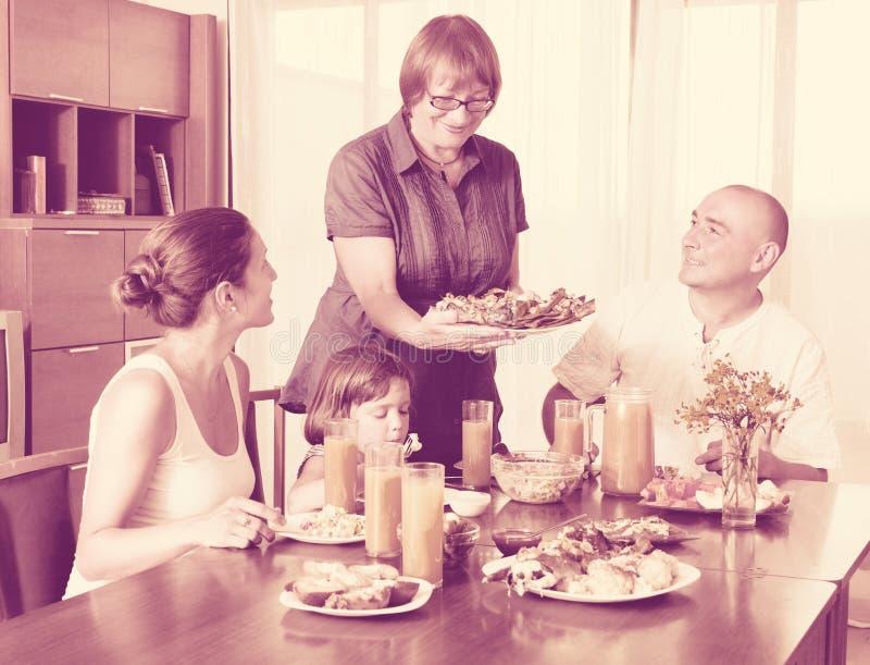 Πορτρέτο της ευτυχούς multigeneration οικογένειας που τρώει τα ψάρια με το χυμό στοκ φωτογραφία