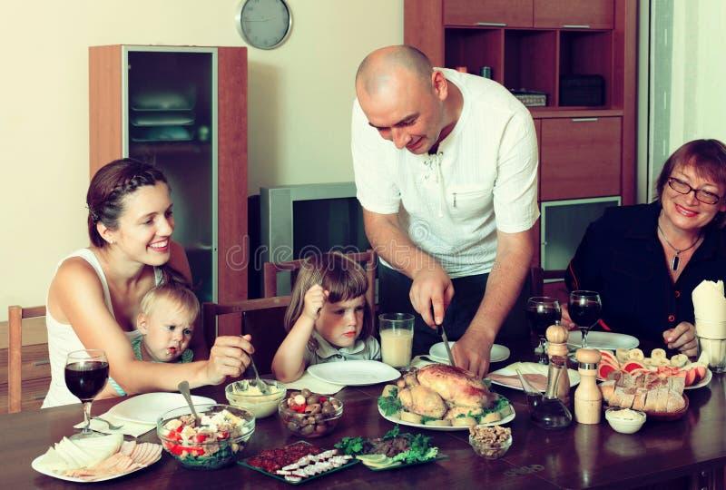 Πορτρέτο της ευτυχούς multigeneration οικογένειας που τρώει το κοτόπουλο με τα WI στοκ εικόνες