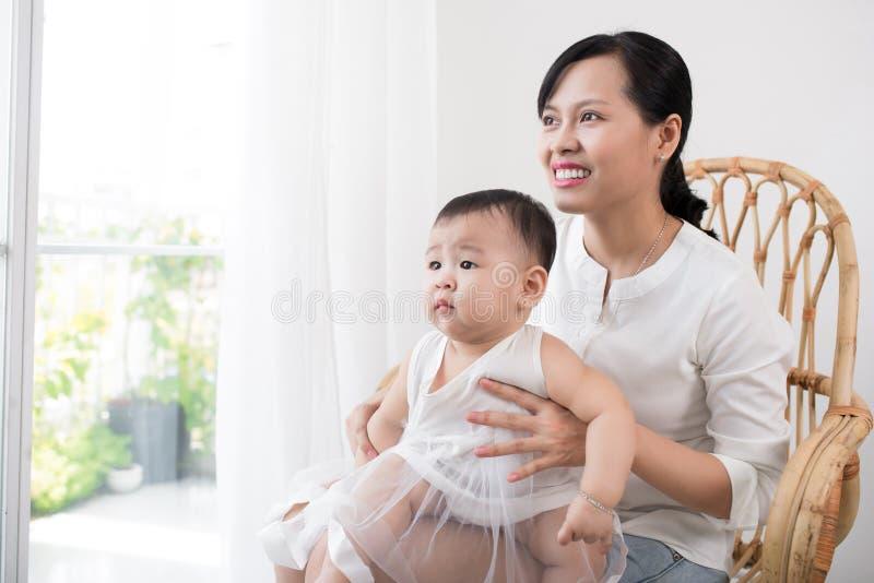 Πορτρέτο της ευτυχών ασιατικών μητέρας και του μωρού που έχουν τη διασκέδαση μαζί στο σπίτι στο άσπρο δωμάτιο, κοντά στο παράθυρο στοκ φωτογραφίες με δικαίωμα ελεύθερης χρήσης