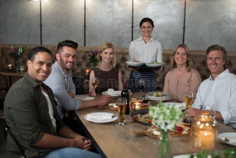 Πορτρέτο της ευτυχών σερβιτόρας και των πελατών να δειπνήσει στον πίνακα στοκ φωτογραφίες με δικαίωμα ελεύθερης χρήσης