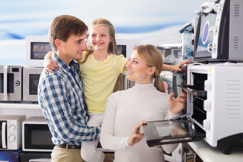 Πορτρέτο της εύθυμης οικογένειας που επιλέγει το μικρόκυμα στοκ φωτογραφία με δικαίωμα ελεύθερης χρήσης