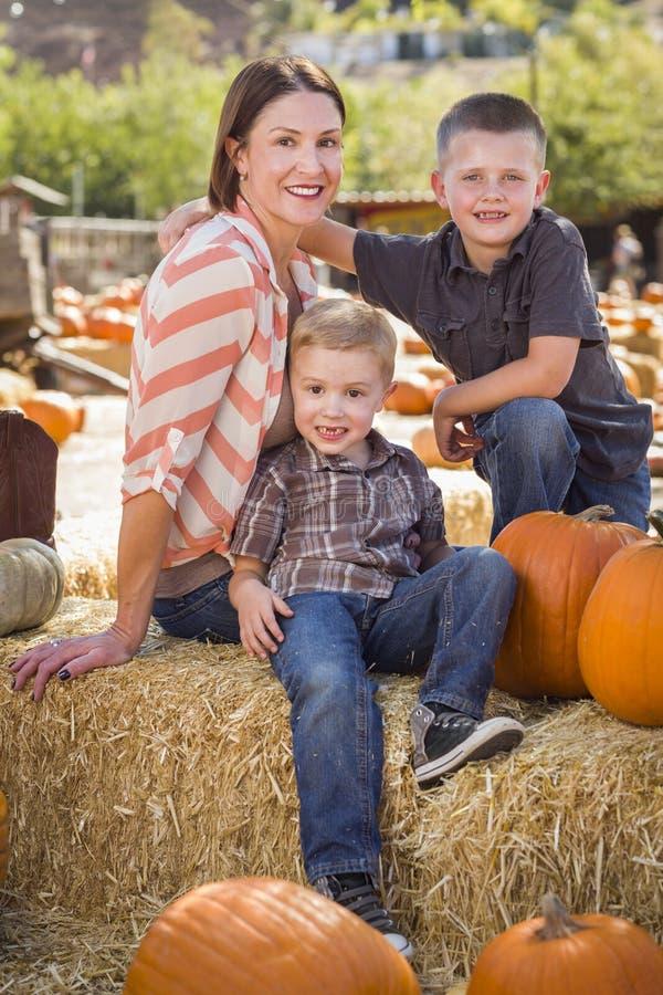 Πορτρέτο της ελκυστικής μητέρας και των γιων της στο μπάλωμα κολοκύθας στοκ φωτογραφία με δικαίωμα ελεύθερης χρήσης