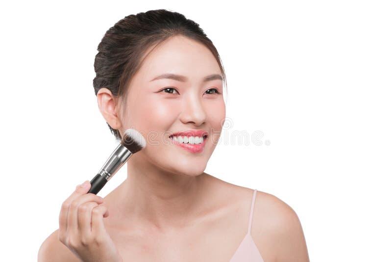 Πορτρέτο της ελκυστικής νέας ασιατικής σύνθεσης εκμετάλλευσης γυναικών brushs στοκ φωτογραφίες