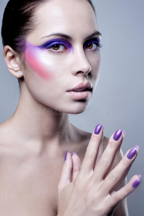 Πορτρέτο της ελκυστικής νέας γυναίκας με το ζωηρόχρωμο makeup στο πρόσωπο στοκ φωτογραφία