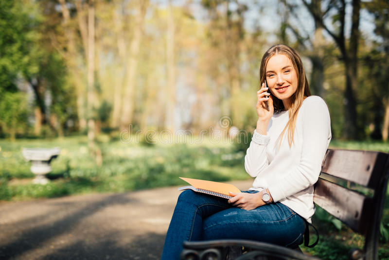 Πορτρέτο της ελκυστικής νέας επαγγελματικής γυναίκας που χρησιμοποιεί ένα smartphone καθμένος σε έναν ξύλινο πάγκο σε ένα πάρκο,  στοκ εικόνες