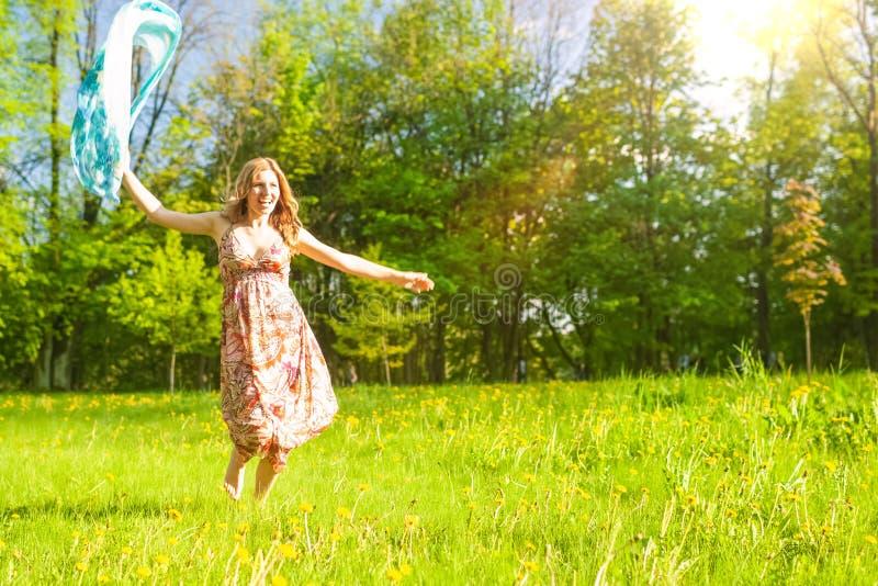 Πορτρέτο της θετικής ευτυχούς καυκάσιας κυρίας Running στο θερινό πάρκο με το πετώντας μαντίλι για το κεφάλι στοκ εικόνες