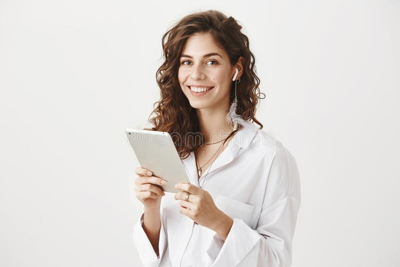 Πορτρέτο της θετικής και επιτυχούς καυκάσιας θηλυκής ταμπλέτας εκμετάλλευσης, μουσική ακούσματος στα ασύρματα earbuds, χαμόγελο στοκ φωτογραφίες