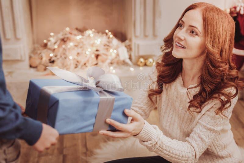 Πορτρέτο της θετικής μητέρας που παρουσιάζει ένα δώρο για το παιδί της στοκ εικόνα
