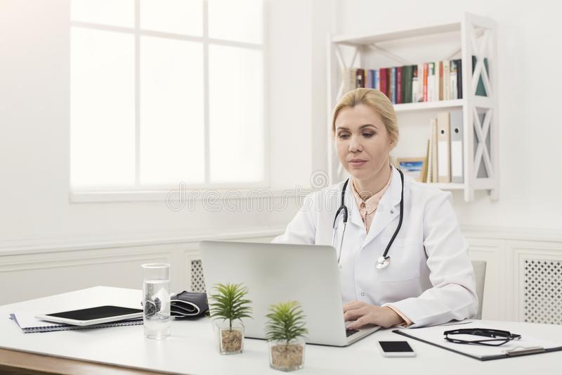 Πορτρέτο της θηλυκής συνεδρίασης γιατρών στον υπολογιστή γραφείου στοκ εικόνες