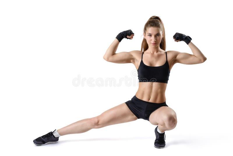 Πορτρέτο της ισχυρής μυϊκής γυναίκας που λυγίζει τους δικέφαλους μυς της και που τεντώνει το πόδι Κορίτσι ικανότητας διακοπής στοκ φωτογραφίες