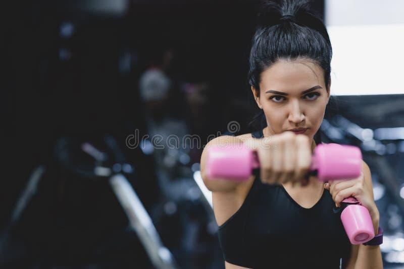 Πορτρέτο της ισχυρής νέας γυναίκας που κάνει την άσκηση με τους αλτήρες Θηλυκό ικανότητας που κάνει την έντονη κατάρτιση στη γυμν στοκ εικόνες