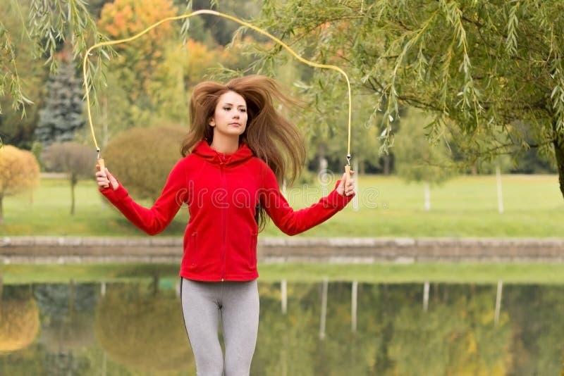 Πορτρέτο της κατάλληλης νέας γυναίκας με το σχοινί άλματος σε ένα πάρκο Θηλυκό να κάνει ικανότητας που πηδά workout υπαίθρια στοκ εικόνα