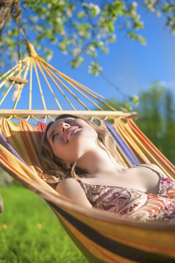 Πορτρέτο της καυκάσιας ξανθής κυρίας Resting σε Hummock κατά τη διάρκεια του χρόνου ανοίξεων στοκ εικόνα