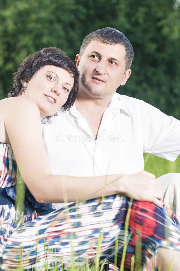 Πορτρέτο της καυκάσιας χαλάρωσης ζεύγους μαζί υπαίθρια στη χλόη στο πάρκο στοκ φωτογραφία με δικαίωμα ελεύθερης χρήσης