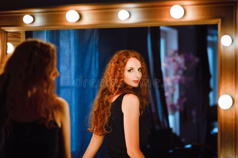 Πορτρέτο της καλής νέας redhead γυναίκας που εξετάζει τον καθρέφτη στοκ εικόνες