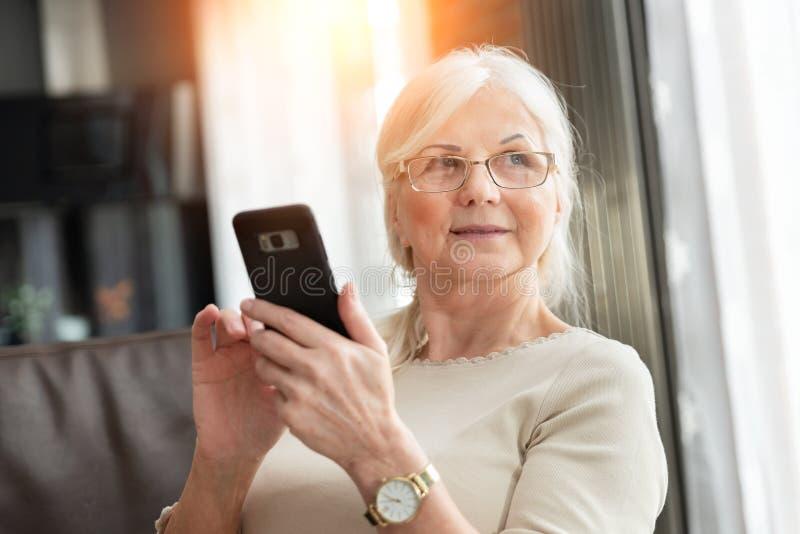Πορτρέτο της κομψής ανώτερης γυναίκας με το έξυπνο τηλέφωνο στοκ εικόνες