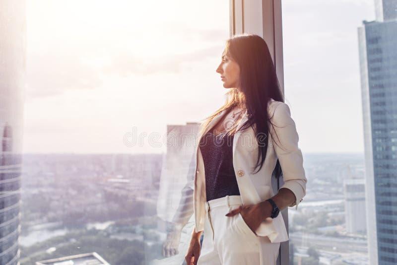 Πορτρέτο της κομψής επιχειρησιακής κυρίας που φορά το άσπρο επίσημο κοστούμι που στέκεται κοντά στο παράθυρο που εξετάζει τη εικο στοκ φωτογραφία