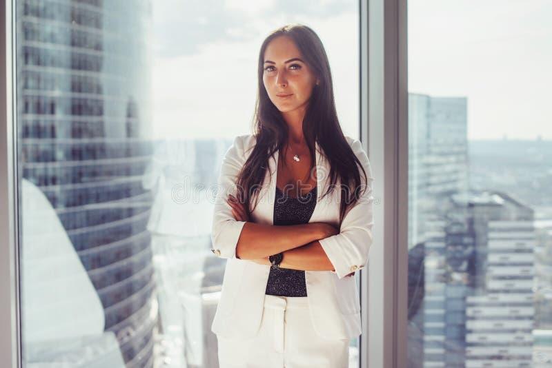 Πορτρέτο της κομψής επιχειρησιακής κυρίας που φορά το άσπρο επίσημο κοστούμι που στέκεται κοντά στο παράθυρο που εξετάζει τη κάμε στοκ εικόνες