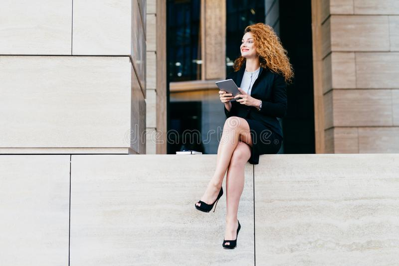 Πορτρέτο της κομψής πανέμορφης γυναίκας στο μαύρο κοστούμι και τα ψηλοτάκουνα παπούτσια που έχουν τα λεπτά μακριά πόδια, που κάθε στοκ φωτογραφία με δικαίωμα ελεύθερης χρήσης