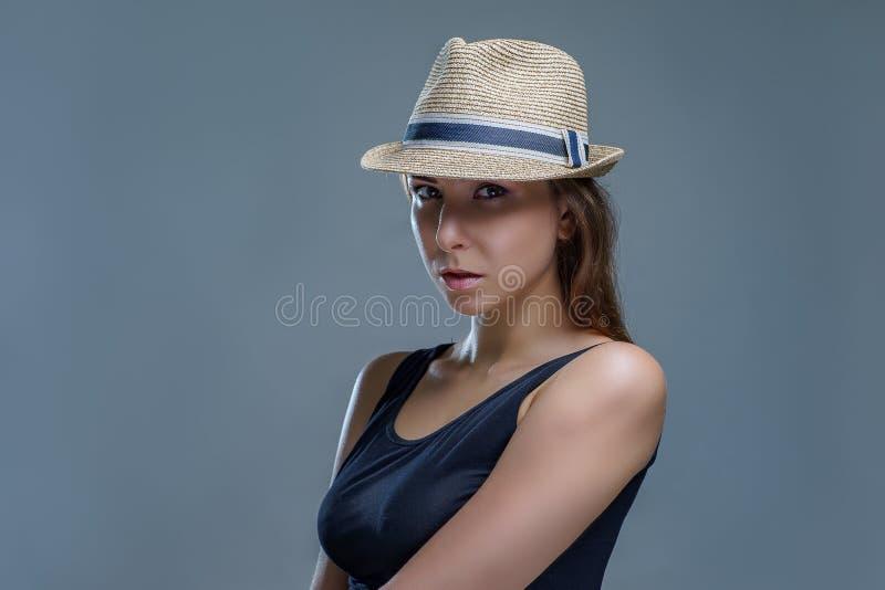 Πορτρέτο της κομψής όμορφης νέας γυναίκας σε ένα μαύρο καπέλο πουκάμισων και μόδας που απομονώνεται στο γκρίζο υπόβαθρο στο στούν στοκ φωτογραφία
