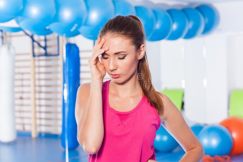 Πορτρέτο της κουρασμένης γυναίκας που έχει το υπόλοιπο στο σύντομο διάλειμμα μετά από το workout στοκ εικόνα