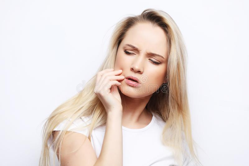 Πορτρέτο της λυπημένης γυναίκας που έχει τον πονόδοντο και σχετικά με το μάγουλο στοκ εικόνες