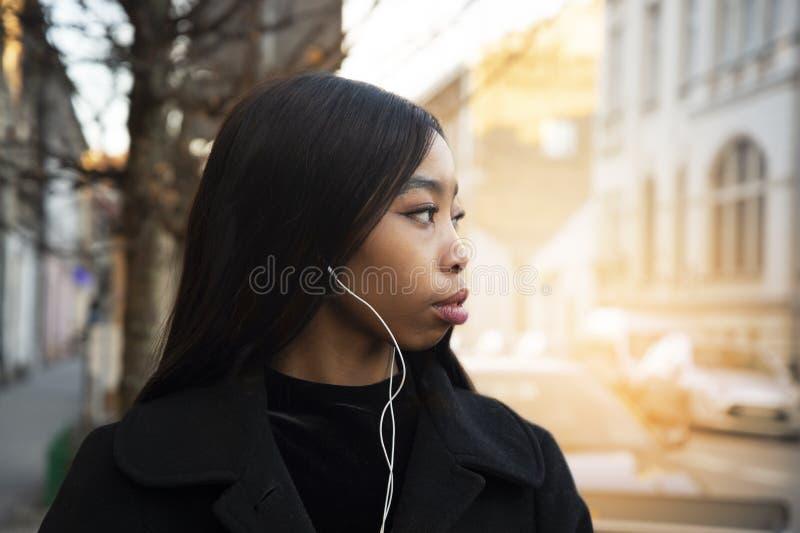 Πορτρέτο της μακρυμάλλους αφρικανικής γυναίκας εφήβων με το άσπρο ακουστικό και του μαύρου παλτού στο υπόβαθρο πόλεων οδών φωτός  στοκ εικόνες