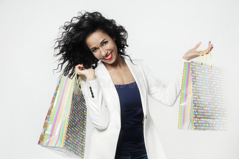 Πορτρέτο της μαύρης γυναίκας ευχαριστημένο από τις τέλειες τσάντες εγγράφου αγορών, πρόσωπο χαμόγελου στοκ φωτογραφία