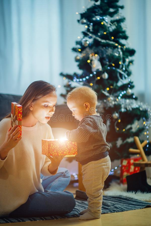 Πορτρέτο της μητέρας και του μωρού κοντά στο χριστουγεννιάτικο δέντρο, ευτυχής έννοια διακοπών, οικογένεια στοκ εικόνα