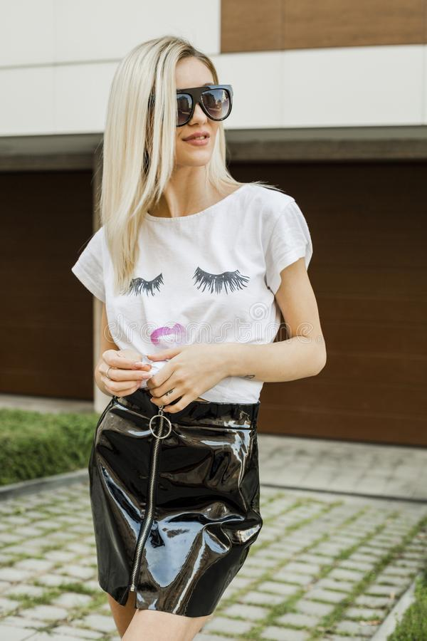 Πορτρέτο της μοντέρνης νέας γυναίκας στην άσπρες μπλούζα και τη φούστα στοκ εικόνα