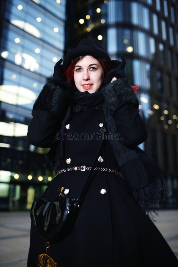 Πορτρέτο της μοντέρνης νέας ευτυχούς γυναίκας στο μαύρο παλτό και του καπέλου ενάντια στο σύγχρονο κτήριο στοκ εικόνες με δικαίωμα ελεύθερης χρήσης
