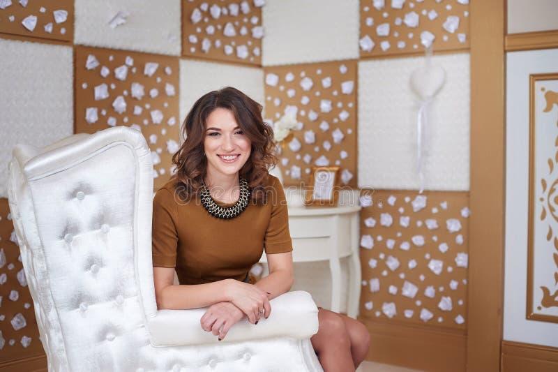Πορτρέτο της μοντέρνης πρότυπης νέας συνεδρίασης γυναικών σε μια άσπρη καρέκλα στοκ φωτογραφίες