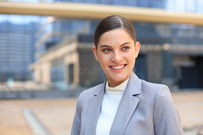 Πορτρέτο της μοντέρνης χαμογελώντας επιχειρησιακής γυναίκας στα μοντέρνα ενδύματα στη μεγάλη πόλη που κοιτάζει σκόπιμα μακριά στοκ φωτογραφία