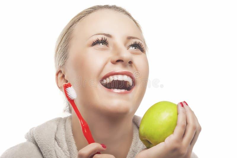 Πορτρέτο της νέας γελώντας ξανθής γυναίκας στην ντύνοντας εκμετάλλευση εσθήτων στοκ εικόνα με δικαίωμα ελεύθερης χρήσης