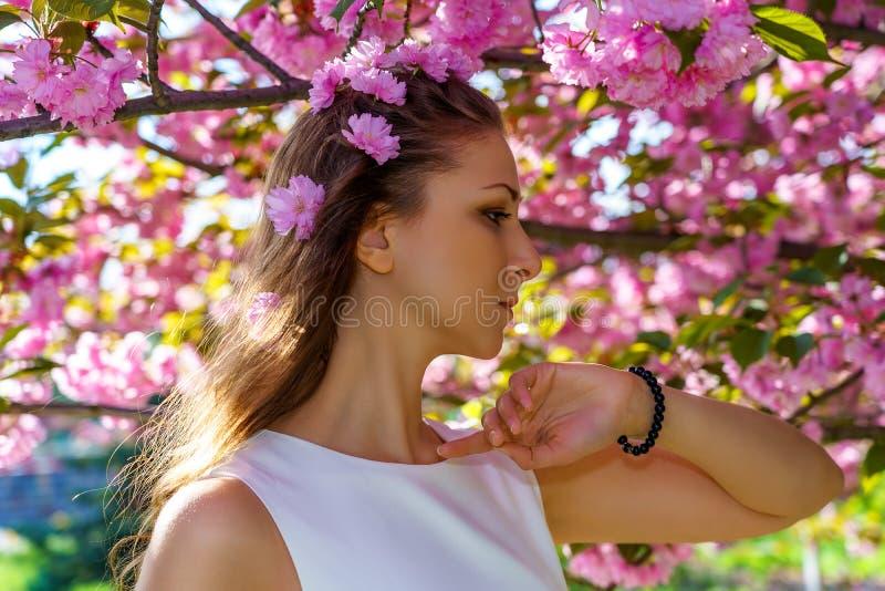 Πορτρέτο της νέας γυναίκας με τα ρόδινα λουλούδια στην τρίχα της στο δέντρο sakura ανθών στοκ φωτογραφία