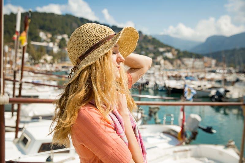 Πορτρέτο της νέας γυναίκας με την ελαφριά σγουρή τρίχα στο καπέλο αχύρου στοκ εικόνες