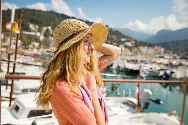 Πορτρέτο της νέας γυναίκας με την ελαφριά σγουρή τρίχα στο καπέλο αχύρου στοκ εικόνα