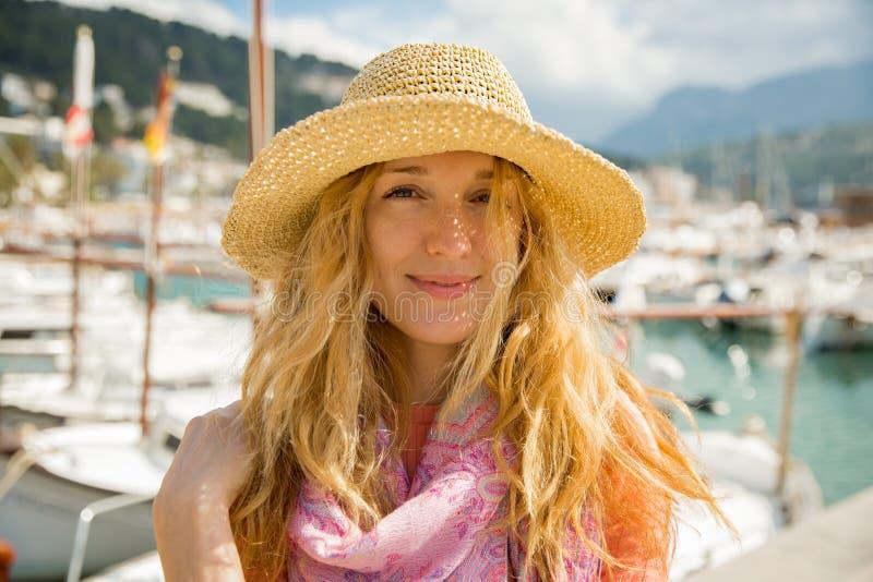 Πορτρέτο της νέας γυναίκας με την ελαφριά σγουρή τρίχα στο καπέλο αχύρου στοκ φωτογραφίες