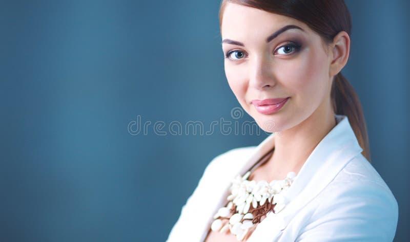 Πορτρέτο της νέας γυναίκας με τις χάντρες, που στέκεται στο γκρίζο υπόβαθρο στοκ φωτογραφίες με δικαίωμα ελεύθερης χρήσης