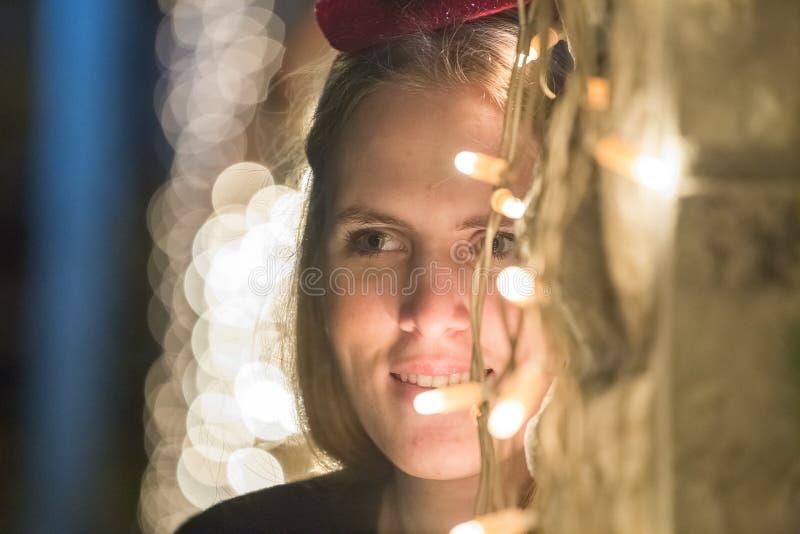 Πορτρέτο της νέας γυναίκας με το καπέλο Χριστουγέννων που στέκεται δίπλα σε Chri στοκ φωτογραφία