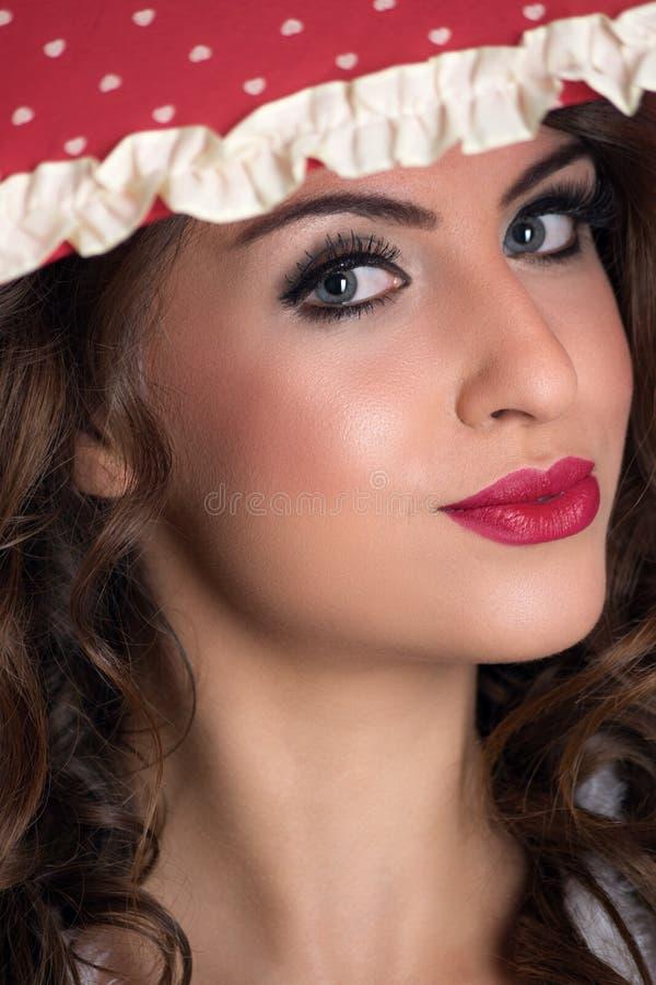 Πορτρέτο της νέας γυναίκας ομορφιάς κάτω από την ομπρέλα με το κόκκινο κραγιόν που εξετάζει τη κάμερα στοκ φωτογραφία