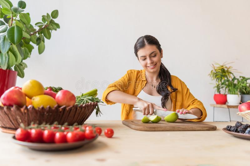 πορτρέτο της νέας γυναίκας που κόβει το φρέσκο μήλο στον ξύλινο τέμνοντα πίνακα στοκ εικόνα