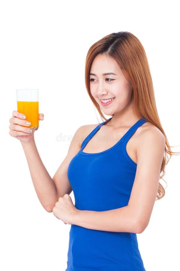 Πορτρέτο της νέας γυναίκας που πίνει το χυμό από πορτοκάλι στοκ φωτογραφία