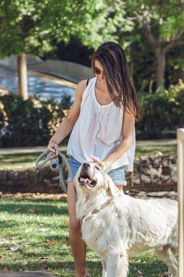 Πορτρέτο της νέας γυναίκας που περπατά το σκυλί της στο πάρκο το καλοκαίρι στοκ φωτογραφίες