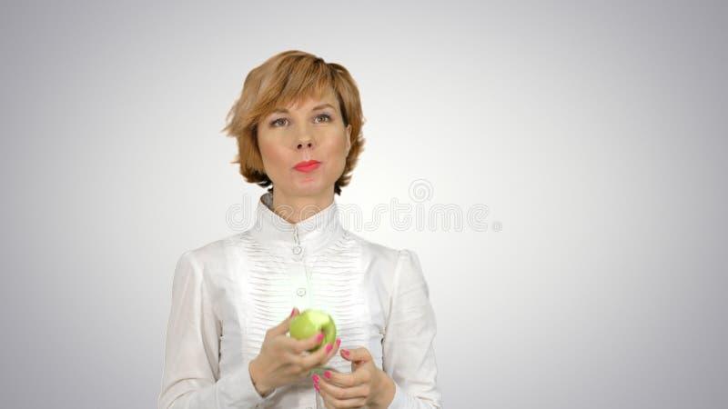 Πορτρέτο της νέας γυναίκας που τρώει το πράσινο μήλο στο άσπρο υπόβαθρο στοκ φωτογραφία με δικαίωμα ελεύθερης χρήσης