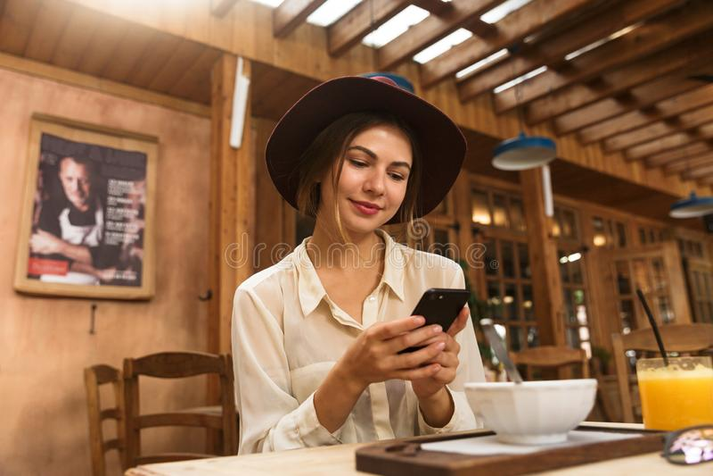 Πορτρέτο της νέας γυναίκας που φορά το καπέλο που χρησιμοποιεί το smartphone στοκ φωτογραφία