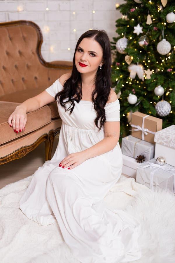 Πορτρέτο της νέας γυναίκας στην άσπρη συνεδρίαση φορεμάτων στο διακοσμημένο livi στοκ εικόνες