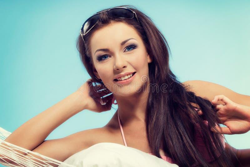 Πορτρέτο της νέας γυναίκας στη χαλάρωση μπικινιών σε μια αιώρα στο χρόνο διακοπών στοκ εικόνες